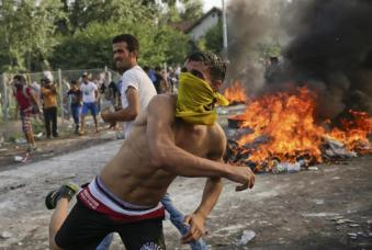 Migrants protest as Hungarian riot police fires tear gas and water cannon at the border crossing with Serbia in Roszke